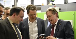 Schulleiter Hartmut Bieber (rechts) erklärte dem Hessischen Kultusminister Alexander Lorz (links) und dem Landtagsabgeordneten Christoph Degen die Herstellung der Kunststofffelge.