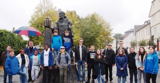Mit Bonifatius auf der gefällten Donar-Eiche: Die Messdienergruppe am Denkmal vor dem Fritzlaer Dom. Diakon Philipp Schöppner mit Schirm.