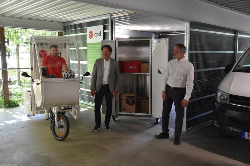 Gerd Seber, Verantwortlicher von DPD, und Markus Henrich, Geschäftsführer der Hanau Parkhaus GmbH (von rechts), gaben den offiziellen Startschuss für den Lastenrad-Mikrohub im Parkhaus am Heinrich-Fischer-Bad